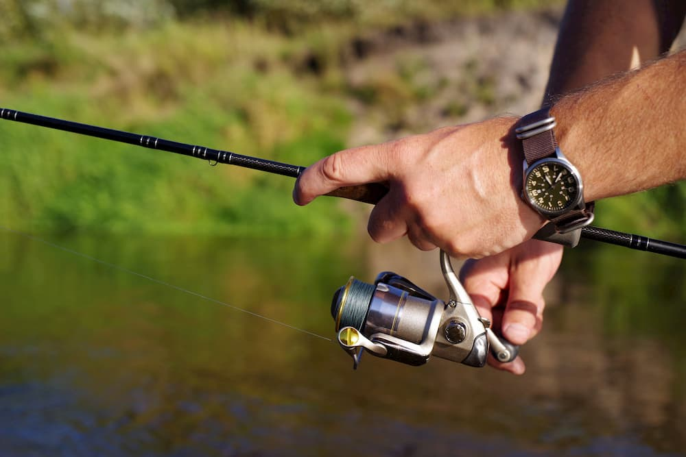 Man fishing with the Pflueger President spinning reel